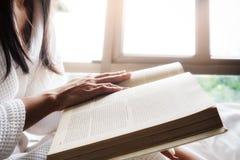 Het lezen van een boek Mooie vrouwelijke zitting op het bed Royalty-vrije Stock Afbeelding