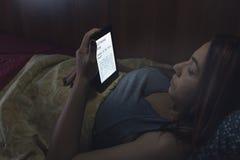 Het lezen van een ebook in bed stock fotografie
