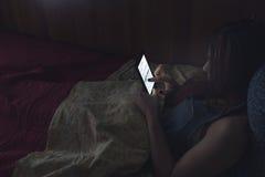 Het lezen van een ebook in bed stock afbeelding