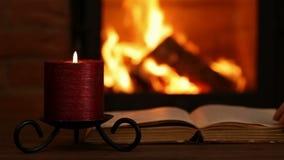 Het lezen van een oud boek bij de open haard in de avond stock video