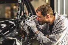 Het lichaam van de werknemersauto het schilderen de winkel controleert de kwaliteit met een microscoop stock afbeelding