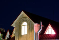 Het licht bij de nacht overspande venster op de hoogste vloer, het roze licht van de driehoekige vensters Stock Afbeelding