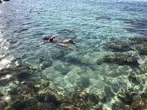 Het licht-gevilde meisje in zwart zwempak zwemt in het duidelijke overzees met gekleurde stenen en turkoois water, hoogste mening stock foto