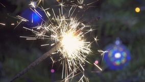 Het licht van Bengalen tegen de achtergrond van een Kerstboom met slow-motion Nieuwjaar` s ballen, stock video