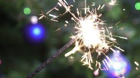 Het licht van Bengalen tegen de achtergrond van een Kerstboom met slow-motion Nieuwjaar` s ballen, stock footage