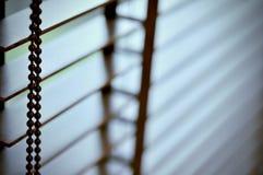 Het licht van de avondzon buiten houten vensterzonneblinden, zonneschijn en schaduw op blind venster en de muur van de Granietteg royalty-vrije stock afbeelding