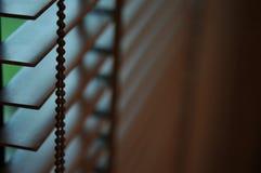 Het licht van de avondzon buiten houten vensterzonneblinden, zonneschijn en schaduw op blind venster en de muur van de Granietteg royalty-vrije stock fotografie