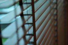 Het licht van de avondzon buiten houten vensterzonneblinden, zonneschijn en schaduw op blind venster en de muur van de Granietteg royalty-vrije stock foto's