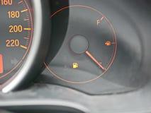 Het licht van de brandstofwaarschuwing op autodashboard is  stock afbeelding