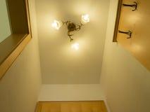 Het licht wordt geschikt rond een cirkelvenster in het plafond van een hoger-woonplaatseetkamer het kunstmatige licht gedeeltelij Stock Foto