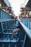 Het lichte haarmeisje stellen op de onvolledige brug die haar benen tonen en het glimlachen een hete dame op een zonnige dag stock fotografie