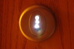 Het lichte overgaan door een sleutelgat stock foto's