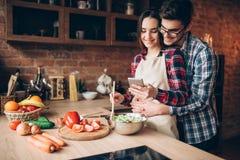 Het liefdepaar bereidt romantisch diner op keuken voor royalty-vrije stock afbeelding