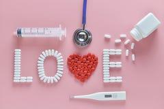 Het LIEFDEwoord maakte van geneeskundepillen, het rode hartvorm uitgieten van witte fles en stethoscoop, naald, temperatuur stock foto's