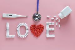 Het LIEFDEwoord maakte van geneeskundepillen, het rode hartvorm uitgieten van witte fles en stethoscoop, temperatuur, op roze ach royalty-vrije stock fotografie