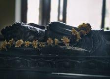 Het liggen Boedha beeldhouwwerk met bloemen Stock Afbeeldingen