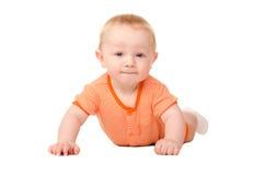 Het liggen grappige babyjongen in sinaasappel Stock Fotografie