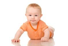 Het liggen grappige babyjongen in sinaasappel Stock Foto's