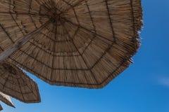 Het liggen onder een stroparaplu en een blauwe hemel royalty-vrije stock fotografie