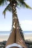 Het liggen van de vrouw tropische strandvoeten die kokosnoot rusten royalty-vrije stock afbeeldingen