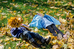 Het liggen van kinderen amogst de herfstbladeren Stock Foto