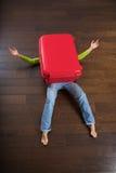 Het liggen vrouw onder rode koffer stock foto's