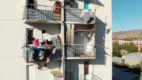 Het linnen is droog op het balkon Oude concrete woningbouw het leven huis in Georgië stock video