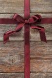 Het lint van Bourgondië met boog op houten achtergrond Stock Foto's