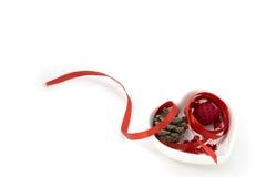 Het lintartpicture van de liefdevorm met rood lint, de kleine kom van de hartvorm en decoratie Royalty-vrije Stock Fotografie
