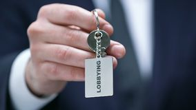 Het lobbyen woord op keychain in mannelijke politicushand, regeringsinvloed stock footage