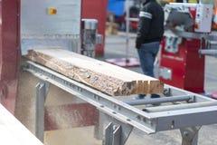 Het logboek, aan de raad wordt gezaagd, komt de zaagmolen die naar voren De houtbewerkingsindustrie royalty-vrije stock foto's
