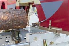Het logboek, aan de raad wordt gezaagd, komt de zaagmolen die naar voren De houtbewerkingsindustrie stock foto