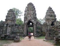 Het lokale meisje berijdt een fiets in tempel in Siem oogst, Kambodja Stock Foto
