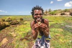 Het lokale strandjongen stellen voor toeristen die kleine krab houden stock foto's