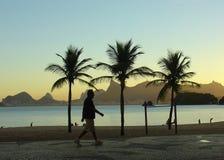 Het lopen bij de zonsondergang op het strand Stock Foto's