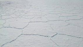 Het lopen door Uyuni Salar in Bolivië Sluit omhoog op de hexagon zoute vlakten stock footage