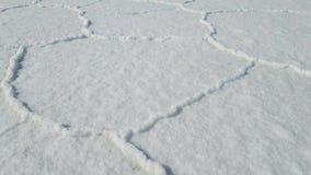 Het lopen door Uyuni Salar in Bolivië Sluit omhoog op de hexagon zoute vlakten stock videobeelden