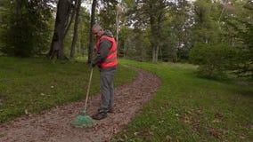 Het lopen en het begin van de parkwerknemer verzamelen bladeren in park stock videobeelden
