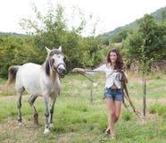 Het lopen met haar paard Stock Afbeelding