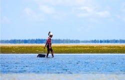 Het lopen met lage wateren en ollecting mosselen in de kust van Mozambique stock foto