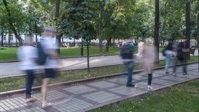 Het lopen onder menigten van mensen langs het brede rijweg met mooi aangelegd landschap Stock Afbeeldingen