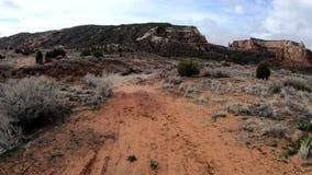 Het lopen onderaan een rode vuilweg dichtbij het Nationale Monument van Colorado stock video
