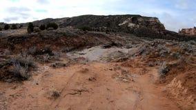 Het lopen onderaan een rode vuilweg dichtbij het Nationale Monument van Colorado stock footage