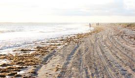 Het lopen op een aangestoken en stil strand Stock Afbeelding