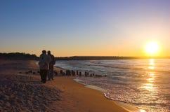 Het lopen op het strand bij zonsopgang Stock Foto