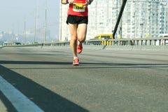 Het lopen op stadsweg Marathon die in het ochtendlicht lopen Jonge mens die op de weg van de stadsbrug lopen De voeten van de atl royalty-vrije stock foto