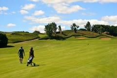 Het lopen van de golfspeler en van het theebusmeisje stock afbeeldingen