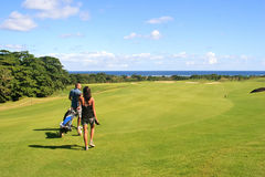 Het lopen van de golfspeler en van het theebusmeisje Stock Foto's