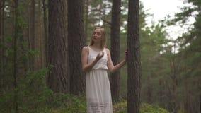 Het lopen van de mooie jonge bosnimf van de blondevrouw in witte kleding in altijdgroen hout stock video