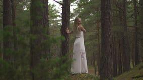 Het lopen van de mooie jonge bosnimf van de blondevrouw in witte kleding in altijdgroen hout stock footage